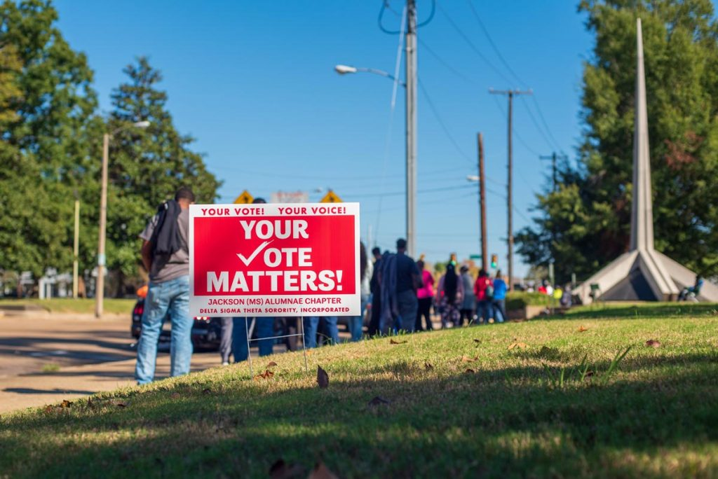 """voters stand lined outside a polling place with a sign in front of them reading, """"Your vote matters"""""""