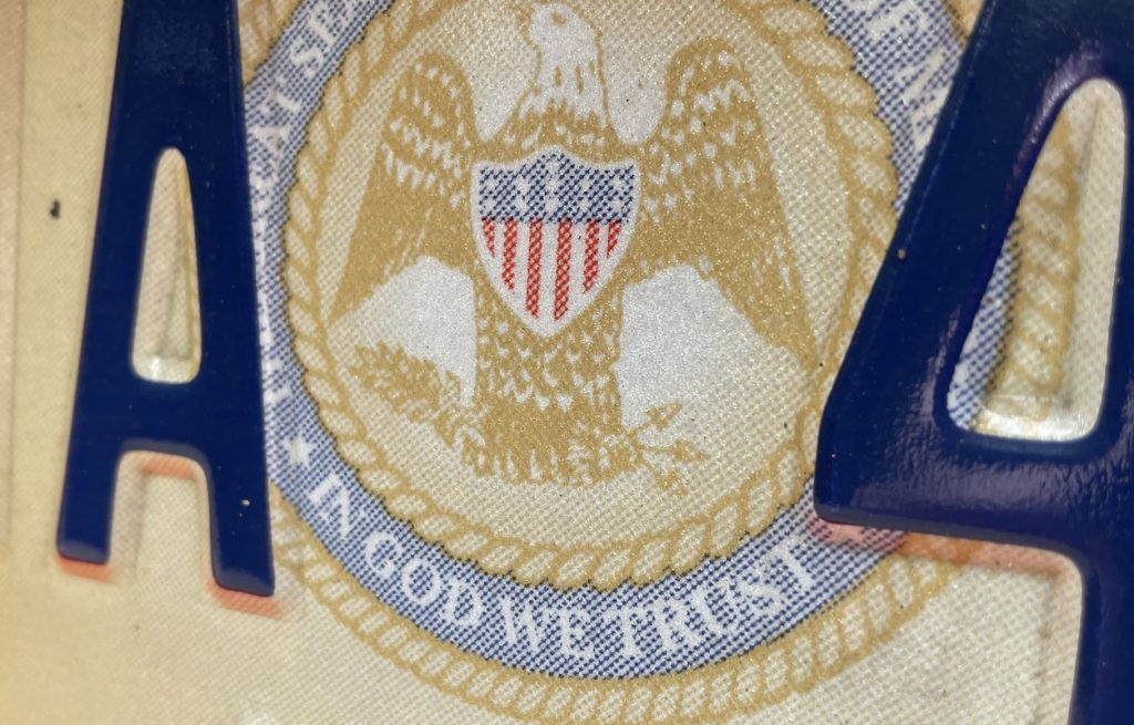 """A Mississippi license plate containing the State Seal with the words """"In God We Trust"""""""