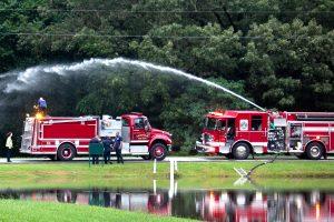 Fire trucks pumping water beside a flooded area