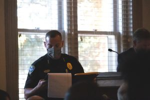 Caption: Oxford Police Chief Jeff McCutchen, wearing a uniform and a mask, looks at a legal pad in front of windows