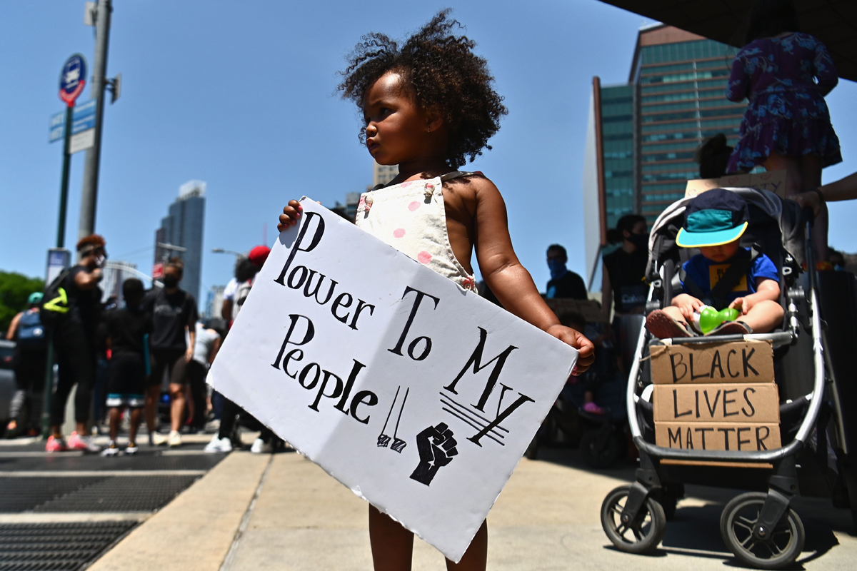 """A young black girl holding a sign reading """"power to my people"""" with other protestors in the background"""
