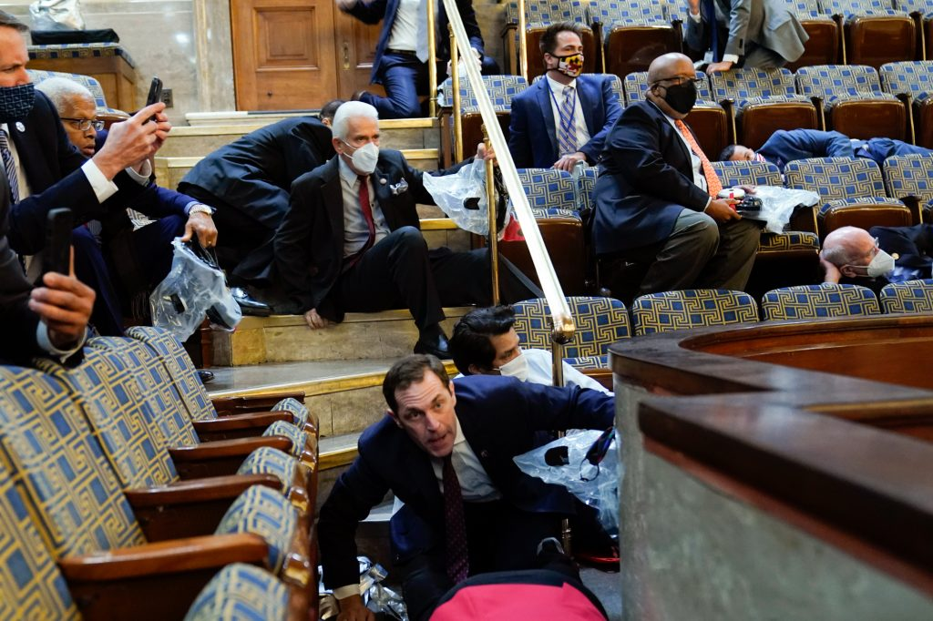 Bennie Thompson sits in the House gallery while other members of Congress lie on the floors of the gallery or hide beneath their chairs during the insurrection