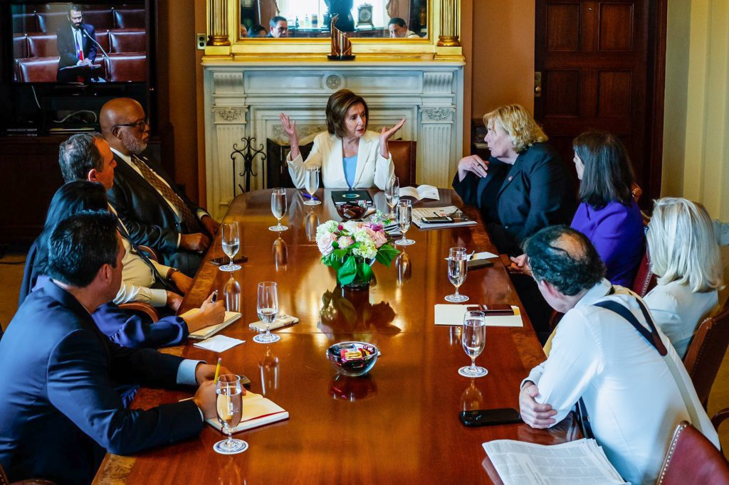 Nancy Pelosi sits at a table with Bennie Thompson and the other Jan. 6 Select Committee members she picked