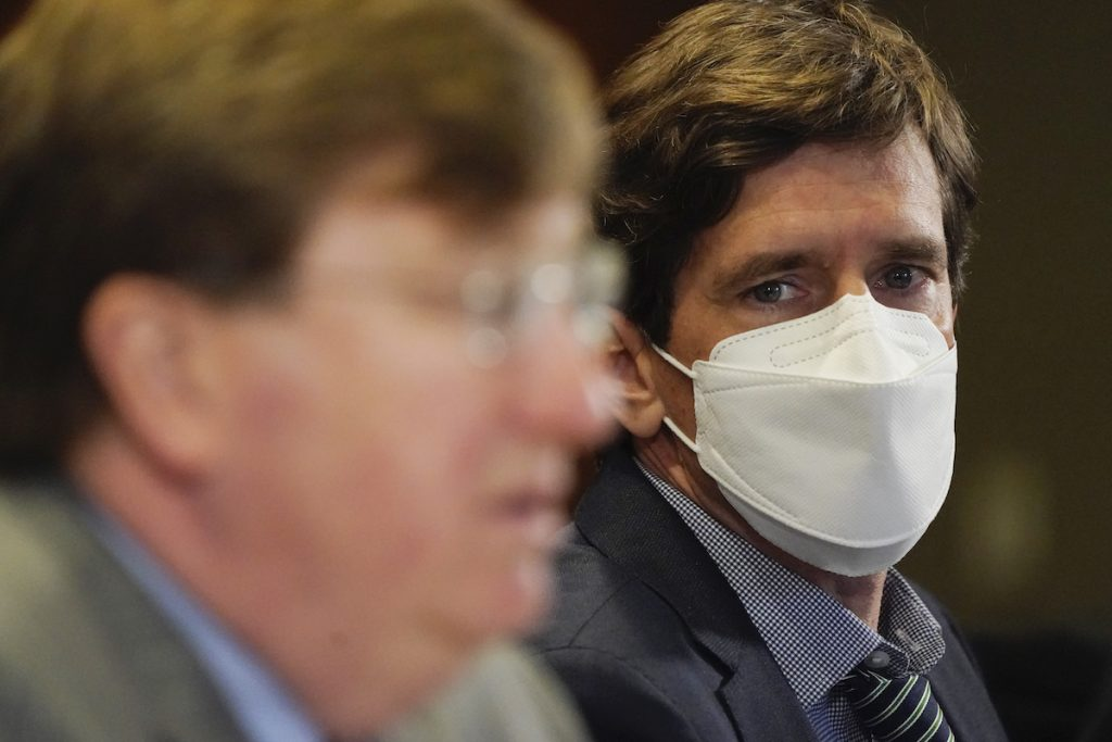 Mississippi State Health Officer Dr Thomas Dobbs looks at Governor Tate Reeves while wearing a mask during a press conference. He is now concerned about the Delta variant that is spreading in the state