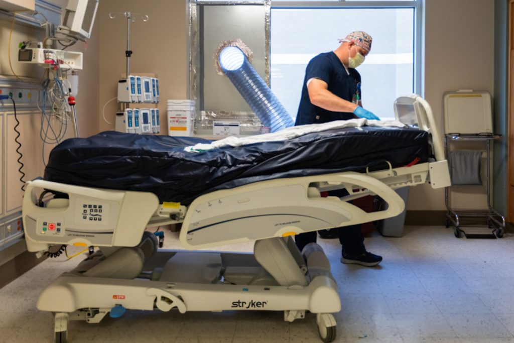 a nurse prepares a hospital bed for an ICU patient