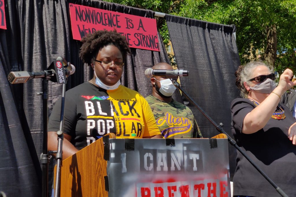 Taylor Turnage speaks on a stage at the BLM Sip march