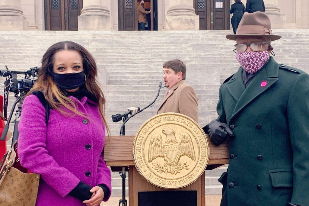 Crystal Welch and Senator Hillman Frazier, wearing masks, stand outside the Mississippi Capitol