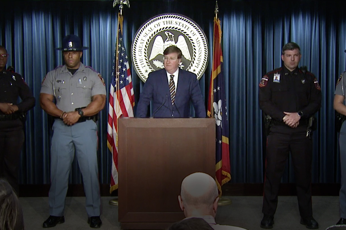 Tate Reeves at podium with uniformed officers on either side
