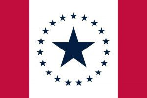 The Stennis flag is seen. It featured a large blue star on the top of a white field with 19 stars around it. Red bands are on either side