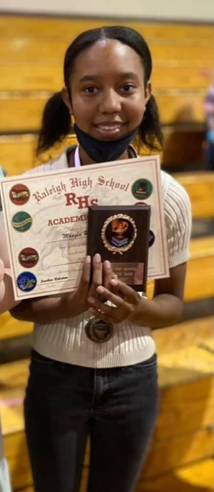 Photo of young Black woman MKayla smiling and holding awards. She is thin and grinning widely