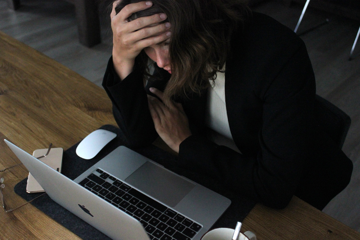 Stressed woman holding her head tilted over laptop