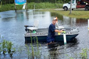 Edward Gonzales navigates his small bass boat throughout the flooded streets of the Shoreline Park community