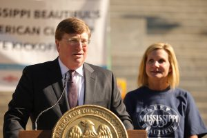 First Lady Elee Reeves watches as Governor Tate Reeves speaks behind a podium
