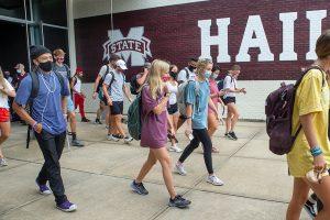 students wearing masks walk around the MSU campus