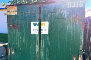 Close up of the side of a green garbage bin with a Waste Management label