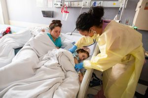 A mother and child in a hospital bed, as a doctor in yellow protective gear looks at the child