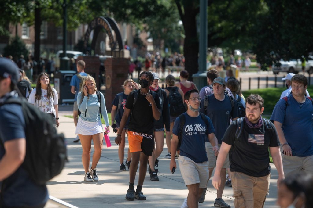 students walking around campus, some wearing masks, at the University of Mississippi