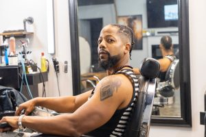Man in a black and white stripped sleeveless shirt sitting in a barber chair, a mirror behind him